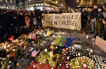 People holding a banner reading  I am Brussels  behind flowers and candles to mourn for the victims at Place de la Bourse in the center of Brussels  Tuesday  March 22  2016  Bombs exploded at the Brussels airport and one of the city s metro stations Tuesday  killing and wounding scores of people  as a European capital was again locked down amid heightened security threats   AP Photo Martin Meissner